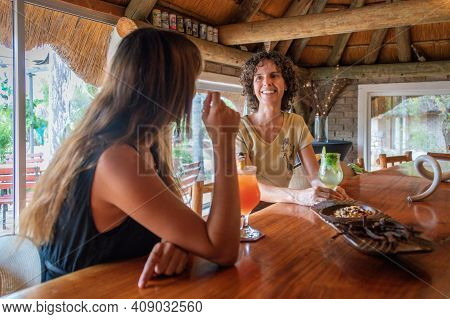 Two Smiling Brunettes Sit In Bar Drinking