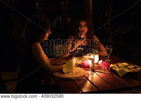 Two Women Drink Wine At Dinner Table