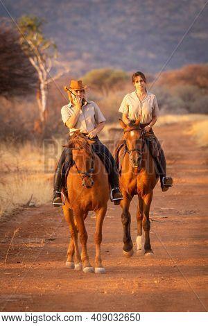 Two Women On Horseback One Using Radio