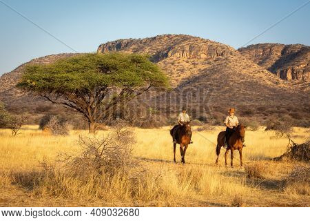 Two Women Ride Past Acacia And Hills