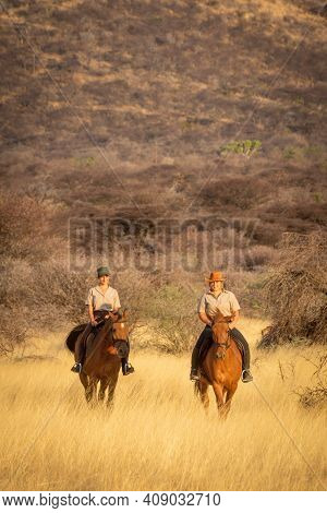 Two Women Ride Through Grass By Hill