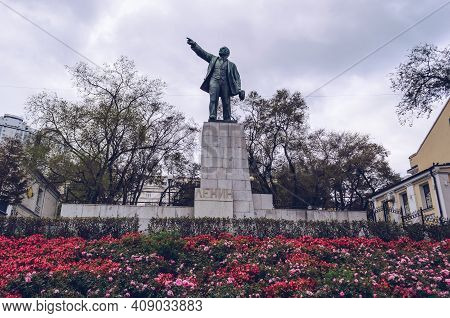 Vladivostok, Russia - October 05, 2020: Close Up View Of Sculpture Of Lenin With Flowerbed Full Of B