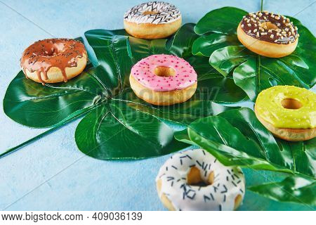 Multicolored Donuts With Frosting, Sprinkles Lie On Monstera Leaves On Blue Background
