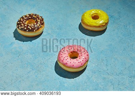 Multicolored Donuts With Frosting And Sprinkles On Blue Background.