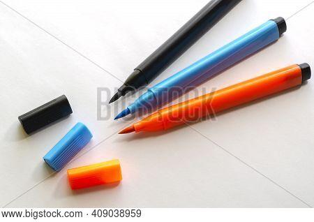 Three New Multi-colored Felt-tip Pen On A White Background. Black, Orange And Blue  Felt-tip Pens Fo