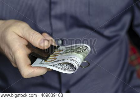 A Man In A Blue Shirt Holds Out Dollars Clamped With A Binder Clip. Several One Hundred Dollar Bills