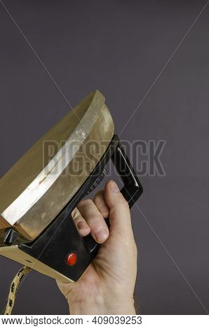 Man's Hand Holds Old Rusty Iron On A Gray Background. Old Metal Iron For Ironing With An Electric Wi