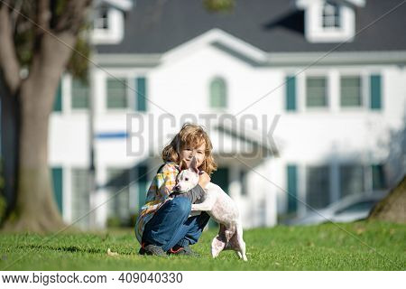 Portrait Of A Little Cute Boy Child With Dog Relaxing On Nature. Child Owner Caressing Gently Her Pe