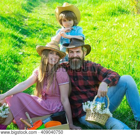 Cheerful Family Sitting On The Grass During A Picnic In A Park. Young Smiling Family Doing A Picnic