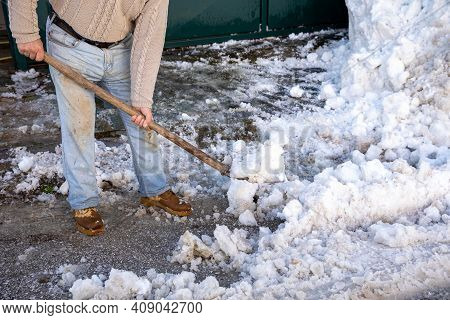 Man With Shovel Cleaning Snow Outside Of His House - Athens, Greece, February 2021.