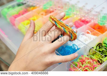Rubber Band Weaving. Knitting Rubber Bands With Loom Knit. Hands Of Girl Hold A Wristband Of Rubber
