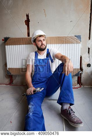 Plumber Leaning On Heating Radiator, Holding Plumber Instruments, Resting On The Floor. Worker With