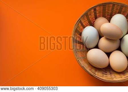 Organic Chicken Eggs In Wicker Basket On Red Background With Copy Space.