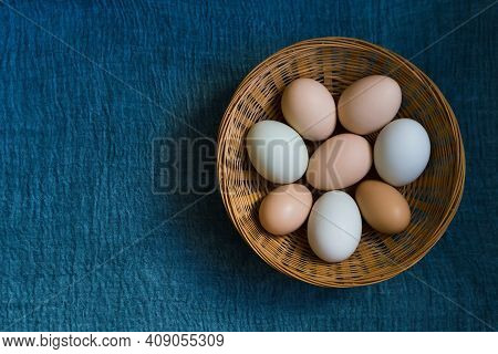 Organic Chicken Eggs In Wicker Basket On Blue Textile Background With Copy Space