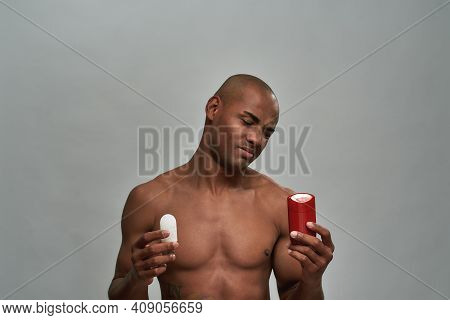 Man Looking With Displeasure On An Empty Package While Keeping A White Crystal Deodorant In Right Ha