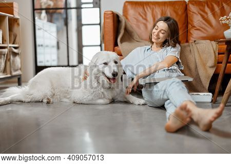Woman Working At Home Sitting With Dog