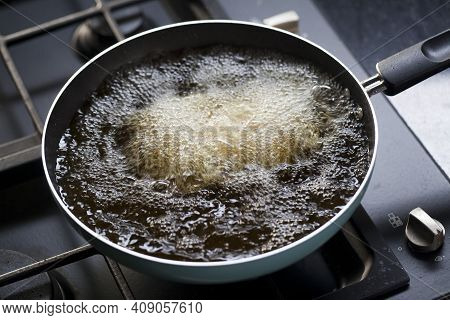 Deep Fried Tofu In A Pan With The Boiling Oil. Cooking In Kitchen.