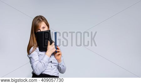 The Concept Of Teaching, Education And University Lifestyle. The Girl Hides Her Face Behind The Diar