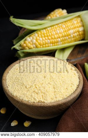 Corn Flour In Bowl And Fresh Cobs On Black Table