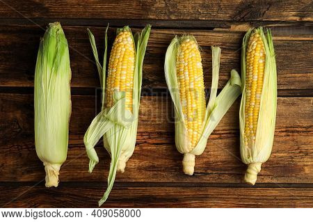 Tasty Sweet Corn Cobs On Wooden Table, Flat Lay