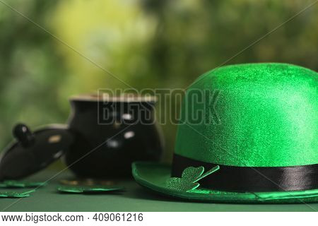 Leprechaun Hat, Clover Leaves And Pot Of Gold On Table Against Blurred Background, Space For Text. S