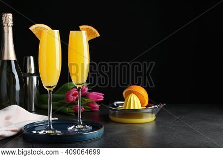 Glasses Of Mimosa Cocktail With Garnish On Grey Table. Space For Text