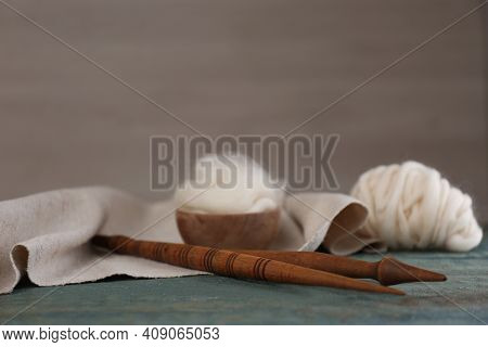 Soft White Wool And Spindles On Blue Wooden Table. Space For Text