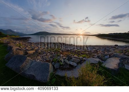 A Rocky Boulder Sea Shore At Sunset. Looking West Near East Suisnish On The Isle Of Raasay, Isle Of