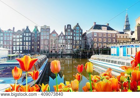 Amsterdam Canal Damrak With Typical Dutch Houses And Moored Boats At Spring Day With Flowers, Hollan