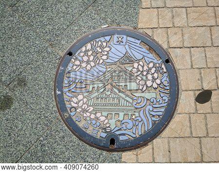 Osaka, Japan - April 4, 2018: Manhole Cover In Osaka, Japan. The Manhole Cover Depicts The Beautiful