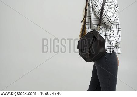 Small Black Leather Bag In A Womans Hand On A White Background. Shoulder Handbag. Woman In A White P