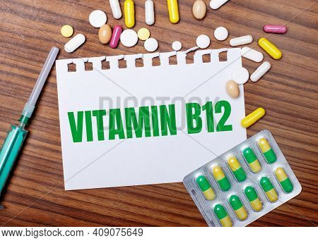 On A Wooden Table, A Syringe, Pills And A Sheet Of Paper With The Inscription Vitamin B12. Medical C