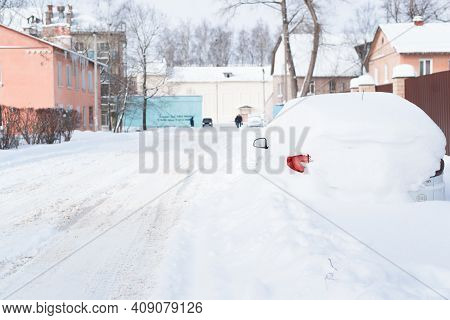 Snow-covered Car, Headlight And Side Mirror On A Winter Street. After A Snowfall, Record Rainfall In