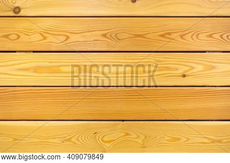 The Light Pine Wall Is Horizontal. Light Yellow Texture With Grooves Between The Boards. Close-up.
