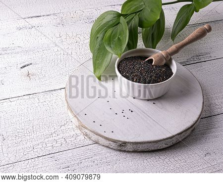 Black Raw Quinoa Seeds And Scoop In White Bowl On White Wooden Table. Few Seeds Are Scattered Around