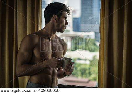 Sexy Young Man Standing Shirtless By Curtains With Coffee