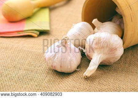 Garlic Bulbs Fall Out Of A Wooden Bowl.