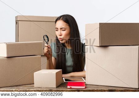 Small Business Owners, Startup And E-commerce Concept. Asian Businesswoman Looking Serious At Box Wi