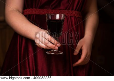 A Glass Of Red Wine On A Red Velvet Dress. The Concept Of A Romantic Dinner. A Glass Of Wine In The