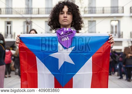 Madrid, Spain - March 8, 2019: Young Woman With Serious Face Displays The Flag Of Puerto Rico During