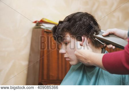The Woman At Home Cuts The Hair Of Her Teenage Son. The Son Is Not Satisfied With His Face Because H