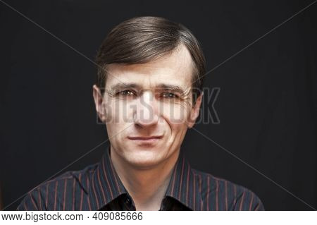 Portrait Of A Man In A Black Shirt With A Sarcastic Angry Face On A Black Background. Horizontal. Co