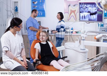Little Girl In Stomatology Office Waiting For Her Teeth Medical Procedure And Examination. Child Wit