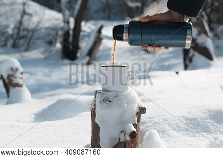 Male Hand Pouring Hot Tea Into A Mug From A Thermos In The Winter Forest. Warming Drink In Cold Weat