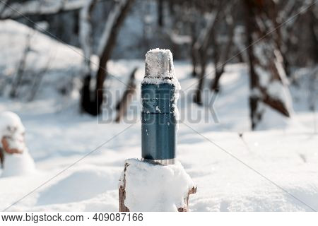 Thermos Covered With Snow, Tree Stump, Winter Forest On A Sunny Day. Blue Vacuum Travel Flask