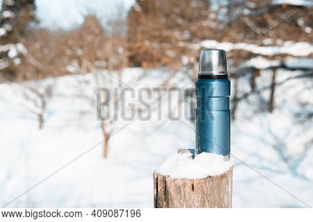 Blue Vacuum Travel Flask. Thermos Covered With Snow, Tree Stump, Winter Forest On A Sunny Day.