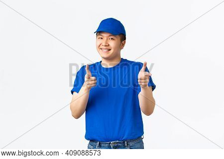 Cheerful Friendly, Smiling Asian Delivery Guy In Blue Cap And T-shirt Pointing Fingers At Camera, Co