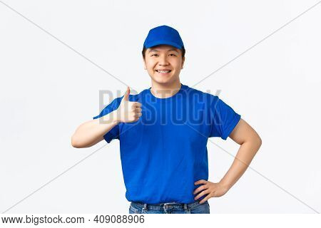 Confident Smiling Asian Courier In Blue Uniform Cap And T-shirt, Showing Thumbs-up Pleased, Guarante