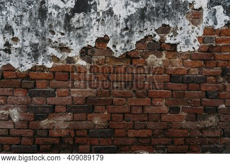 Old And Worn Red Brick Wall Face With White And Black Cement Coating Peeling Away.