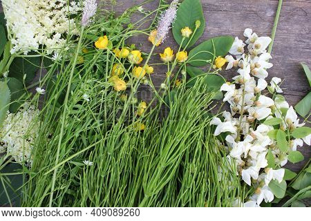 Summer Flowers On Wooden Background. Bunch Of Green Wild Plants And Yellow Buttercups Flower On Rust